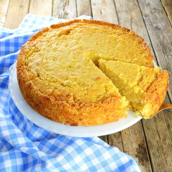 Cornbread on a plate with slice partially removed