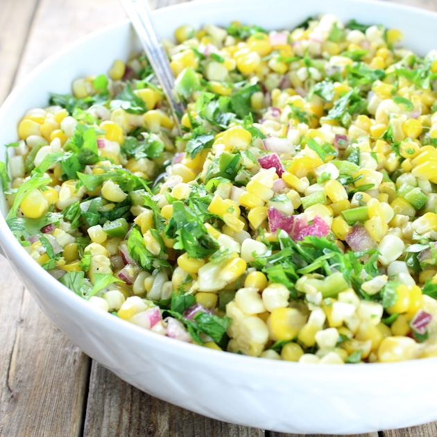 Partial bowl of Jalapeno corn salad with serving spoon