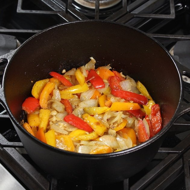 peppers and onions cooking in a large black cast iron pot