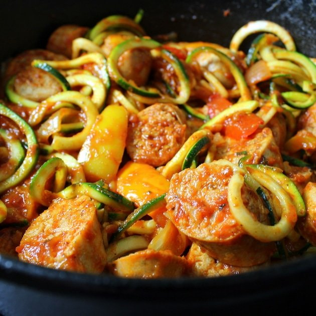 A close up of Italian sausage with peppers and zoodles