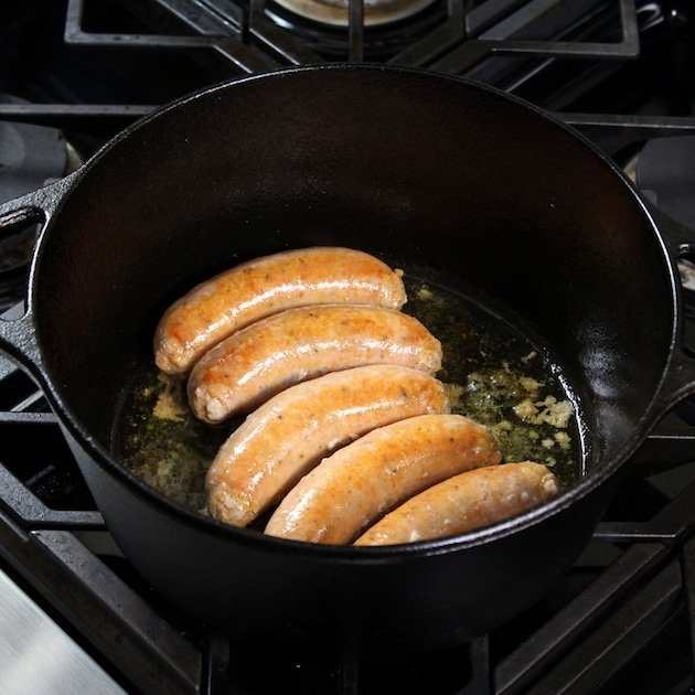 Italian sausages cooking in a large black cast iron pot