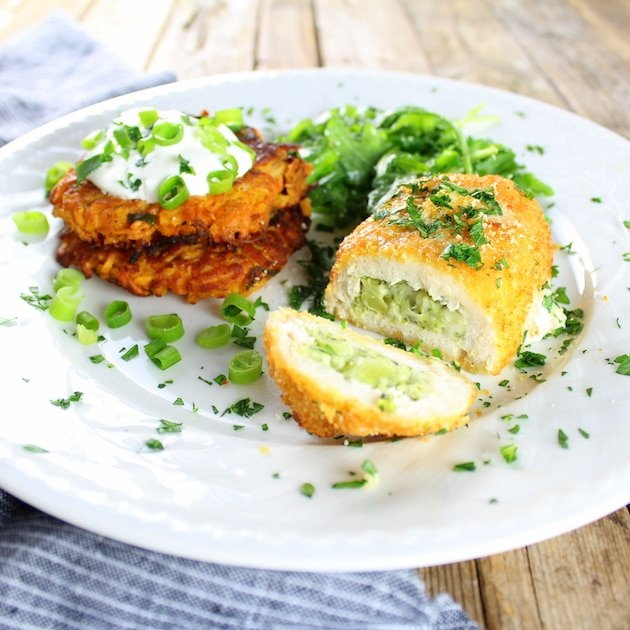 Eye level dinner plate of Parmesan Sweet Potato Cakes With Broccoli Cheese Chicken