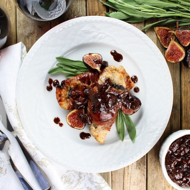 Chicken cutlet wrapped in prosciutto and sage leaves with fig sauce
