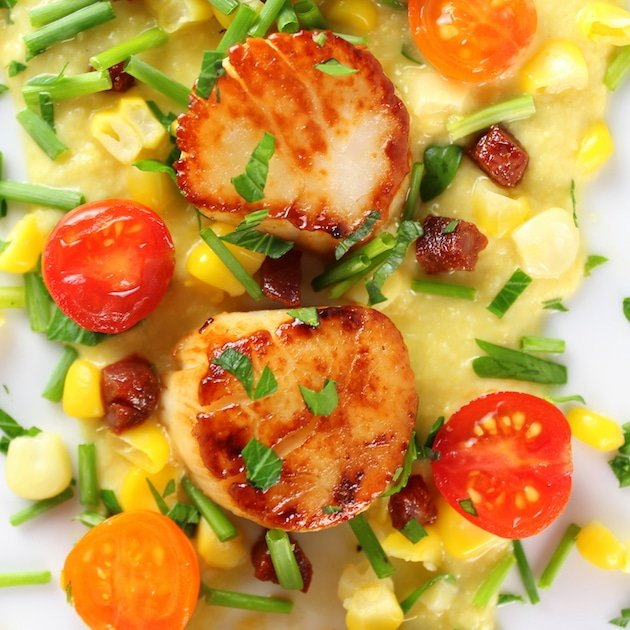 Very Close up over top two seared scallops on a bed of corn puree