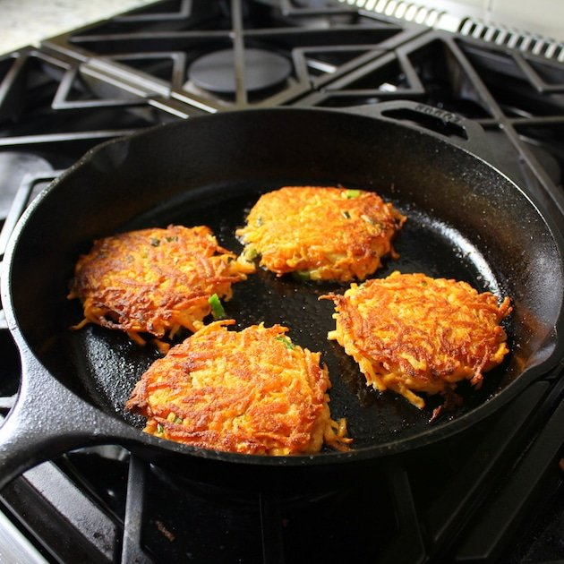 Four Sweet potato cakes frying in a cast iron skillet