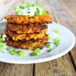 Sweet potato cakes stacked on a plate and topped with sour cream & green onions