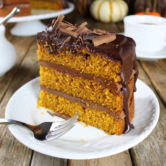 A piece of chocolate cake on a plate, with Pumpkin and Ganache