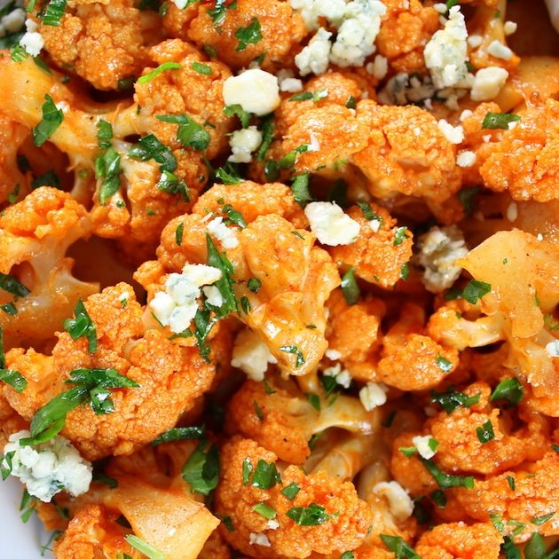 Close up of orange Buffalo Cauliflower with Blue Cheese crumbles