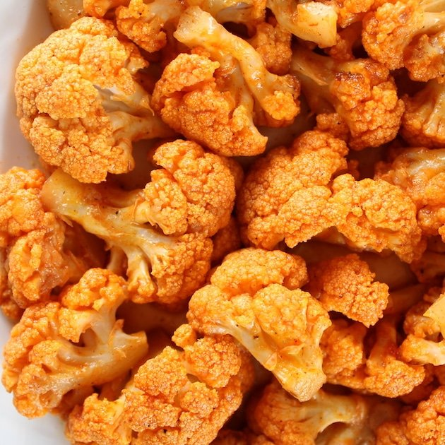 Close up of orange cauliflower that\'s been cooked in buffalo sauce