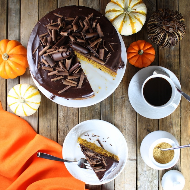 Pumpkin layer cake with chocolate ganache and shaved dark chocolate on table with cup of coffee