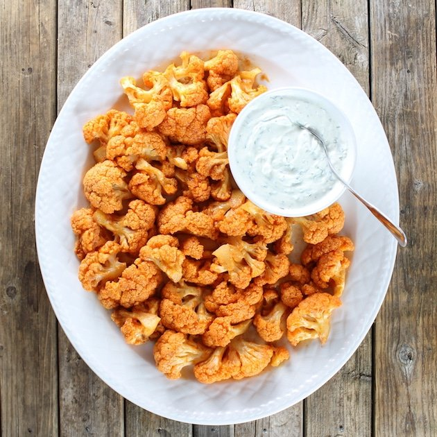 A platter of buffalo cauliflower sitting on top of a wooden table