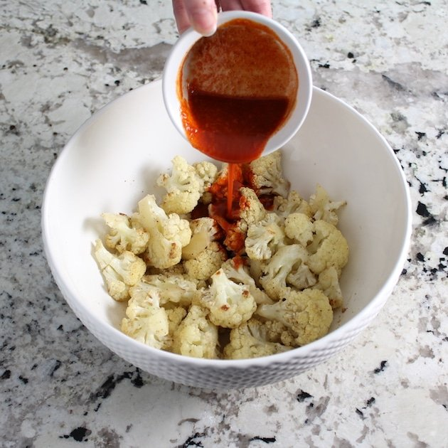 Pouring buffalo sauce over bowlful of roasted cauliflower florets
