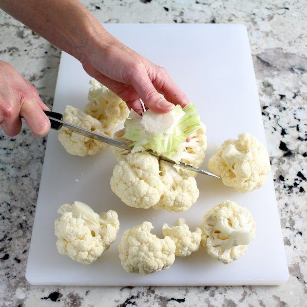 Cutting head of cauliflower on a cutting board