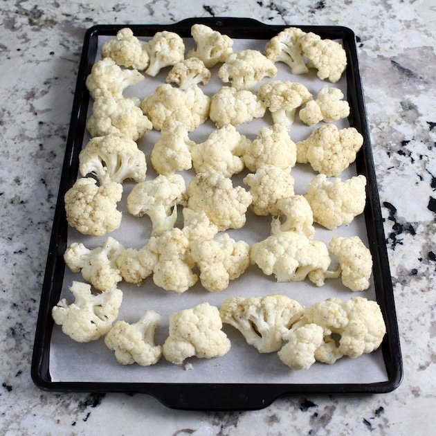 Cauliflower florets on a parchment-lined baking sheet