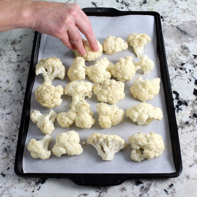 Placing cauliflower florets on a parchment-lined baking sheet