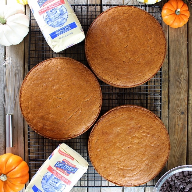 Three cooked pumpkin cake rounds on cooling rack