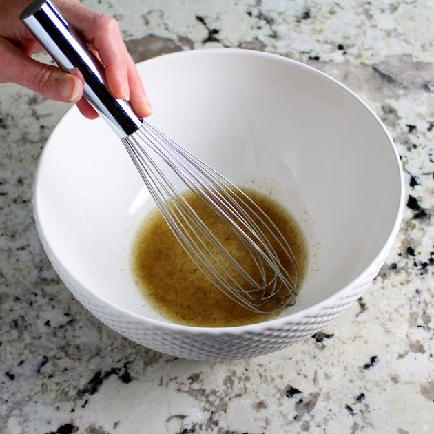 Whisking spices with olive oil in large white bowl
