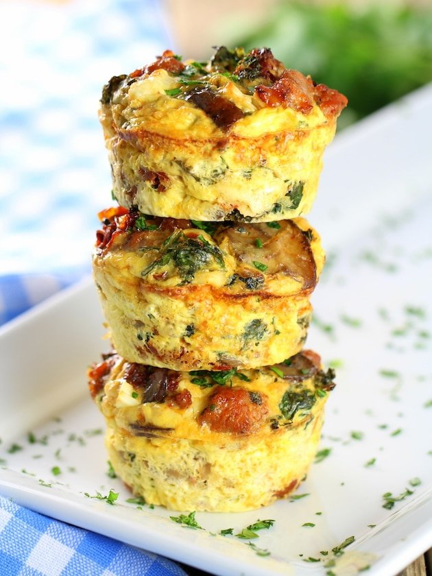 """Three stacked breakfast \""""egg cups\"""" with mushroom, kale, and spinach"""
