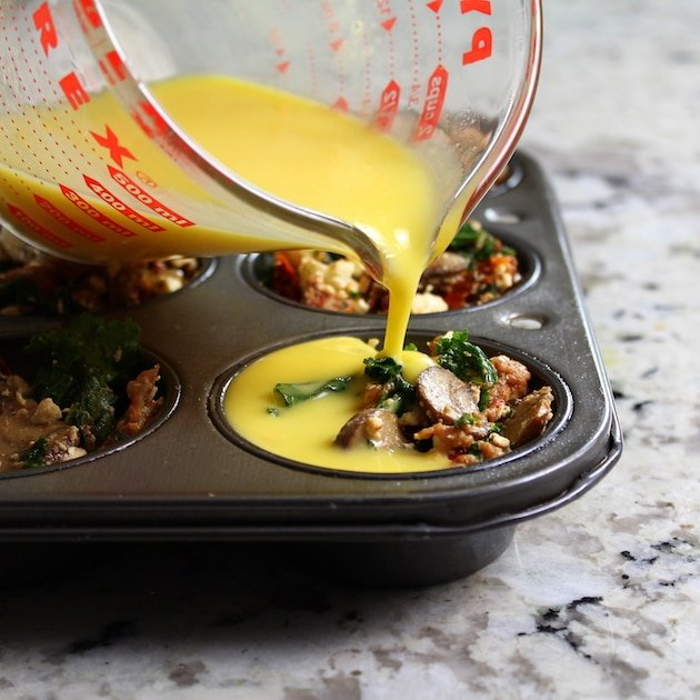 Pouring egg over ingredients in muffin tin to make breakfast cups