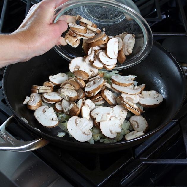adding cremini mushrooms to saute pan