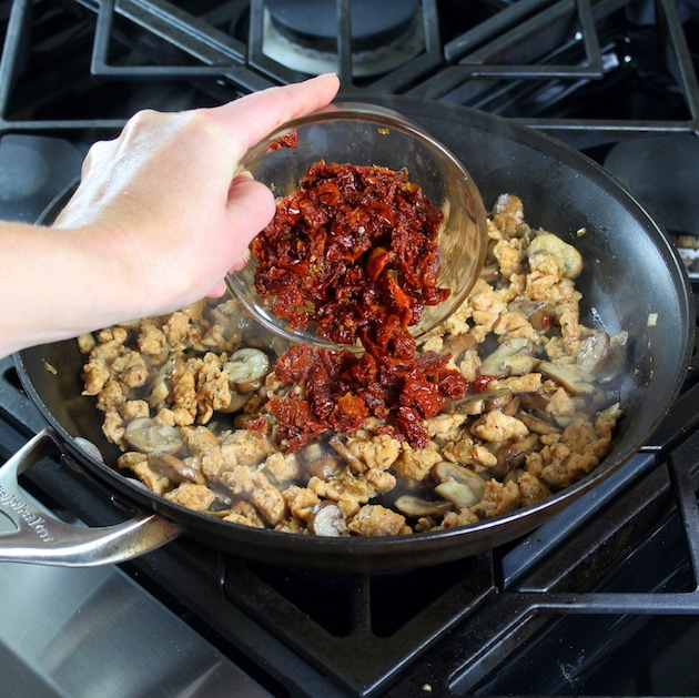 Adding sundried tomatoes to pay with mushrooms and onions