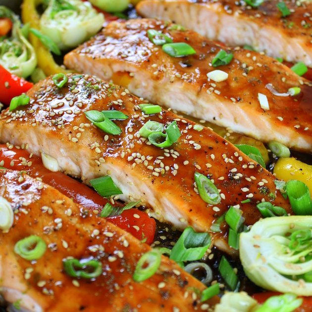 A close up of Salmon filets roasted with honey soy glaze, sesame seeds, and green onions