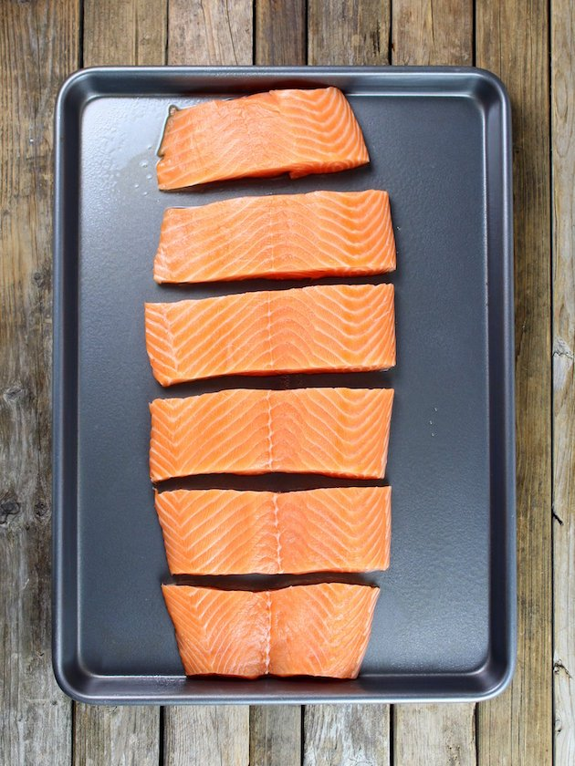 Side of salmon sliced into pieces on a baking sheet ready to cook