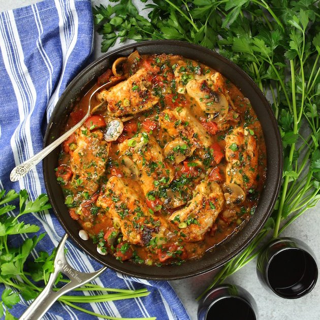 Large skillet with chicken breasts cooked in tomato herb sauce