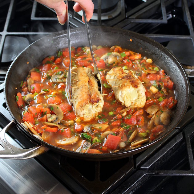 Adding chicken breasts to saute pan with italian red sauce