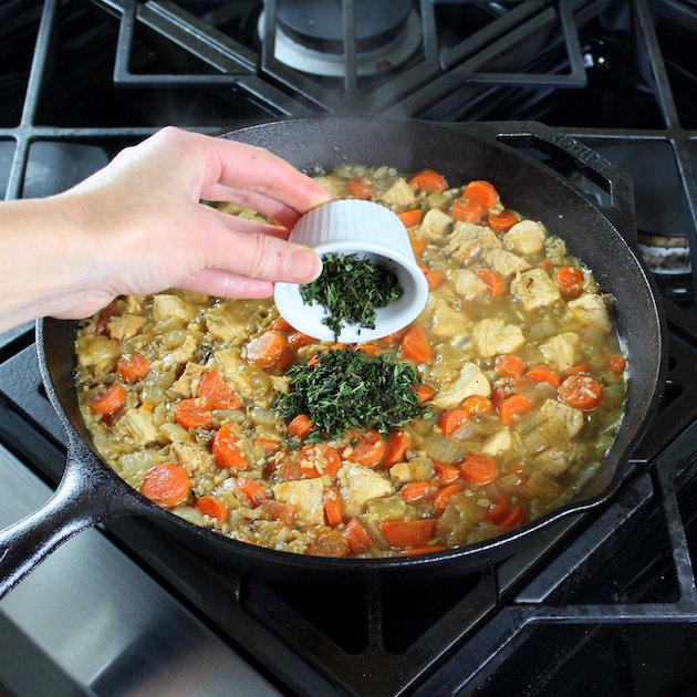 Adding thyme to skillet of cooking vegetables and chicken