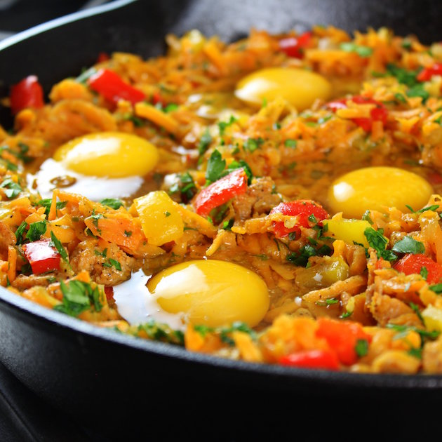 Close up eye level eggs cooking in a breakfast skillet on stovetop