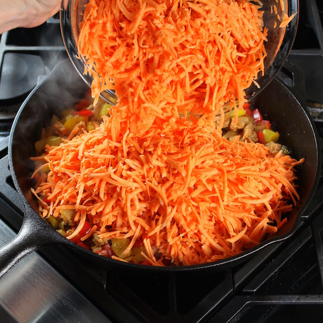 Adding shredded sweet potatoes to a breakfast skillet