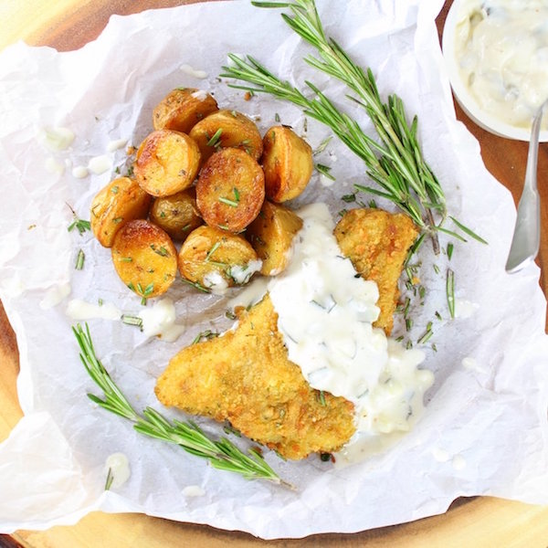 Breaded fish filet with tartar sauce and roasted baby potatoes on parchment paper