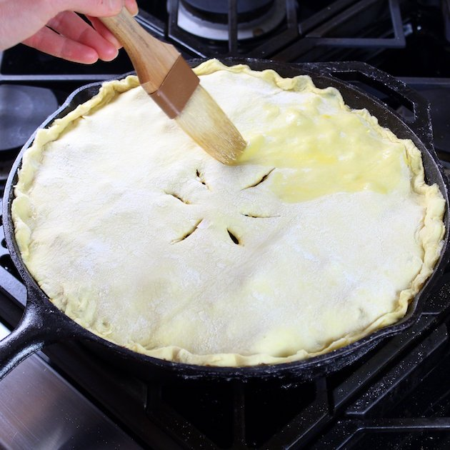 Brushing egg wash on top of pie before baking
