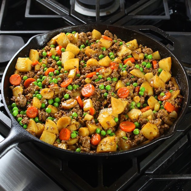 A pan filled with meat and vegetables cooking on a stove