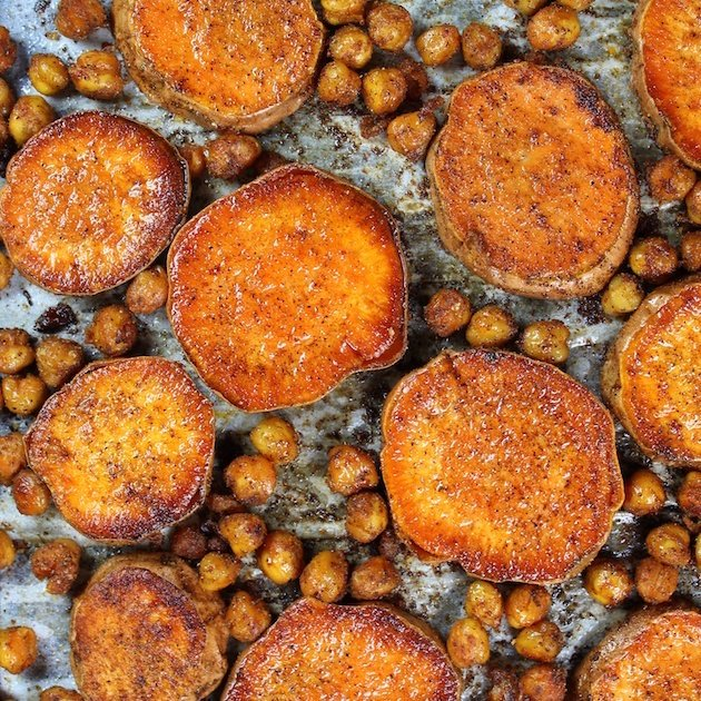 Closeup of sliced baked Sweet Potatoes and Chickpeas on a baking sheet