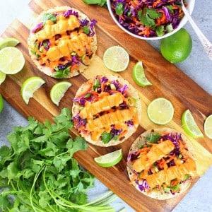 Three fish tacos on a cutting board with slaw and bang bang sauce