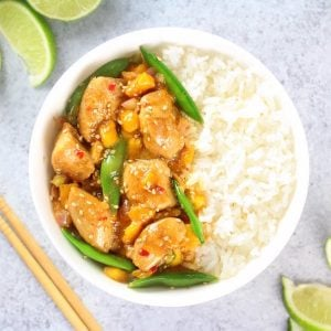 Asian chicken with snap peas, sesame seeds on a bowl of rice