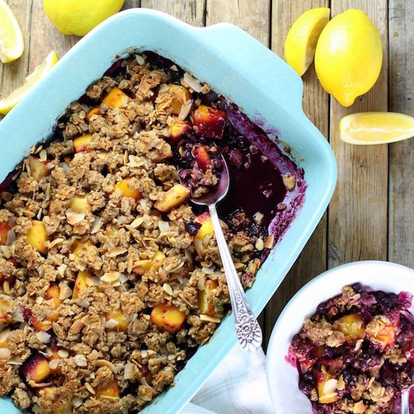 Blue baking dish with blueberry mango dessert topped with crumble mixture