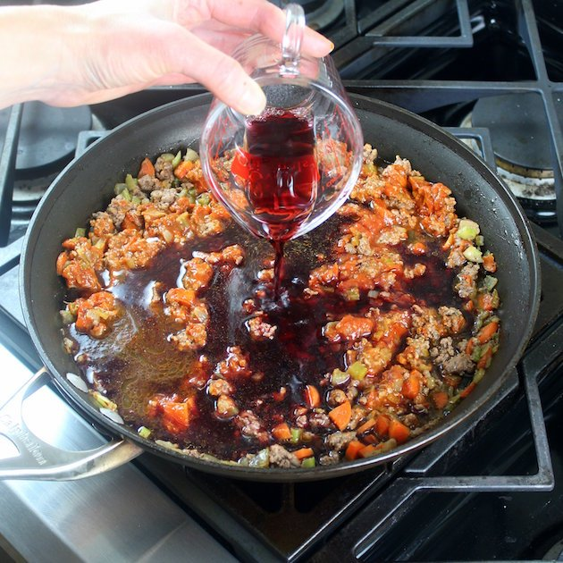 Adding red wine to bolognese cooking on stovetop