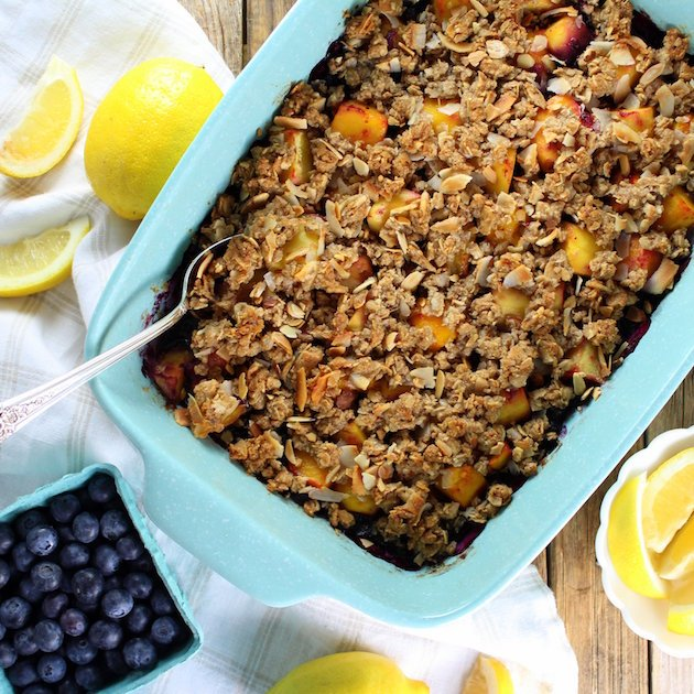 Tropical Blueberry Mango Coconut Crumble in a casserole dish next to fresh lemons and blueberries