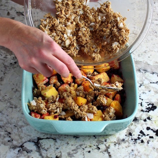 Adding crumble mixture to mangoes and blueberries in a baking dish