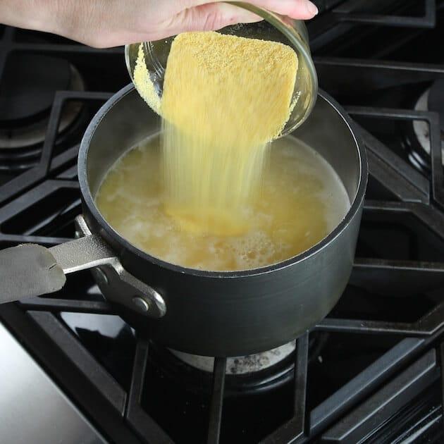 Adding dry polenta to pot on stovetop