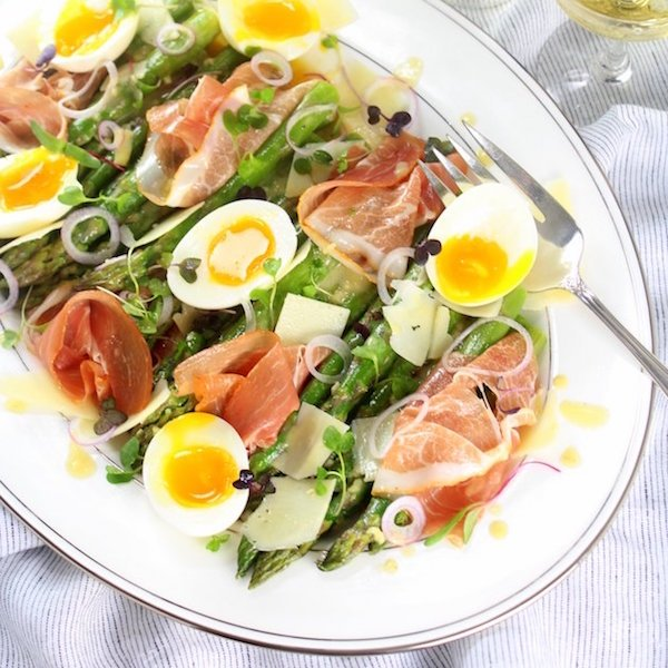 Asparagus, Egg and Prosciutto salad on white oval platter