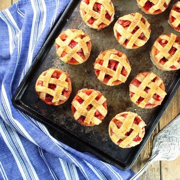 Mini strawberry rhubarb pies on a baking sheet