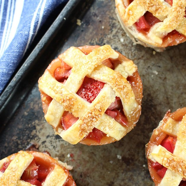Close up of Mini Strawberry Rhubarb Pies on baking sheet
