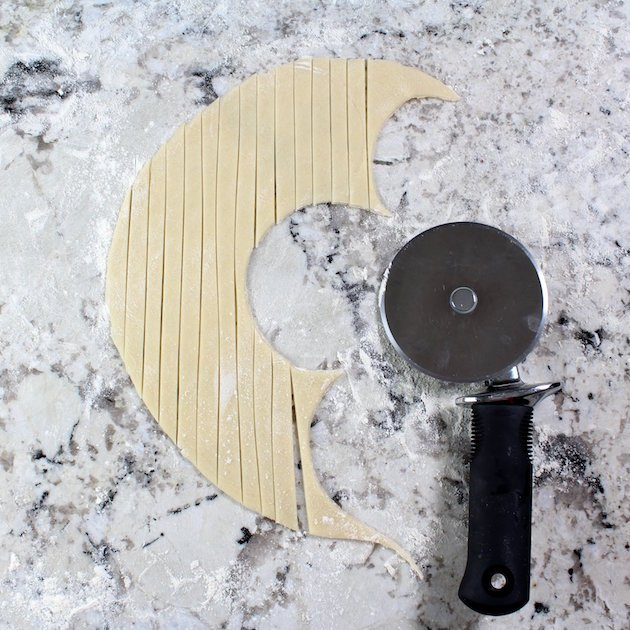 Using pizza cutter to cut pastry dough into thin strips