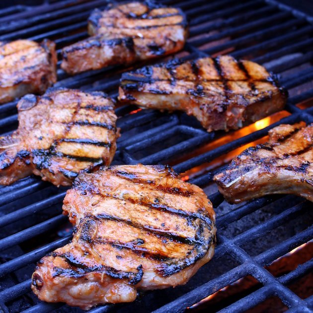 Six Pork chops grilling on grill