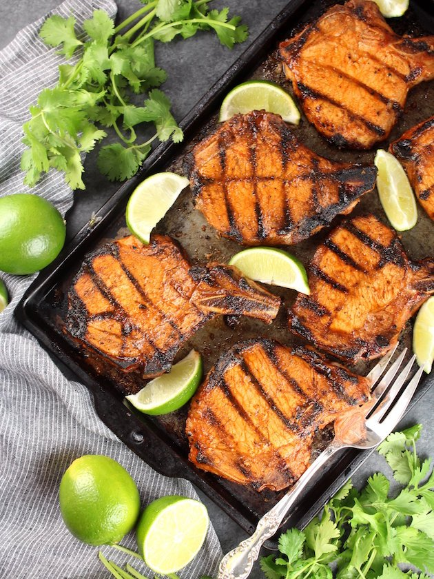 Maple Sriracha Grilled Bone-In Pork Chops  surrounded by limes and cilantro