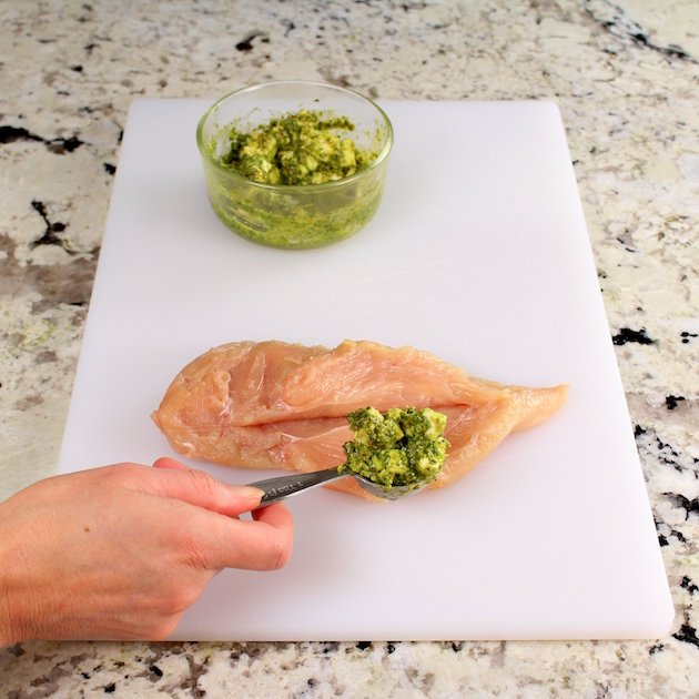 Stuffing a sliced chicken breast with pesto
